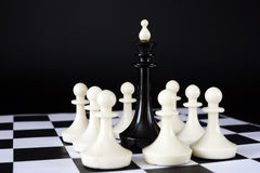 Chess king surrounded by enemy pawns. Defeat and loss. Concept with chess pieces against black background Royalty Free Stock Image