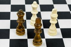 Chess Kings and queens on chessboard. In room Stock Photography