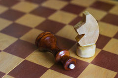 Chess. The knight`s move. Horse overthrew the Queen. Royalty Free Stock Image