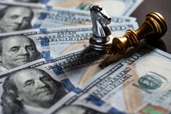 Chess knight stand over the fallen king with US banknote background.. Business competition concept. Copy space play playing finance economy money strategy stock photography