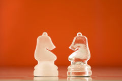 Chess knights. Two knights facing each other on a orange background Stock Photo
