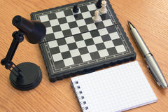 Chess, lamp notebook and pen on the table Royalty Free Stock Photography