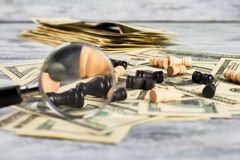 Chess, loupe and dollars. Stock Photos