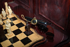 Chess made of natural wood antique pocket watch gun Stock Images
