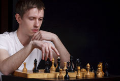Chess master. Making smart move on a black background Royalty Free Stock Photos