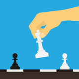 Chess master. Picture of human hand holding chess figure above the board Stock Photo