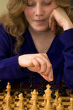 Chess move. Teen woman concentrates on moving her bishop during a game of chess stock photography