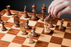 Chess move. Chess pieces on wood chessboard Royalty Free Stock Images