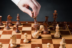 Chess move. Chess pieces on wood chessboard Royalty Free Stock Photography