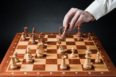 Chess move. Chess pieces on wood chessboard Stock Images