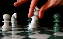 Chess move. Hand moving chess piece, on black background stock photo