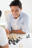 Chess move. Excited teenager contemplating his next chess move Royalty Free Stock Image
