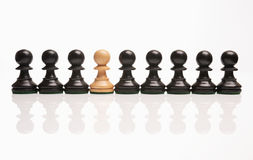Chess the odd one out. White pawn in row of black pawns stock images