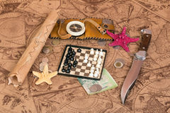 Chess and other items of traveler on old maps Stock Photo