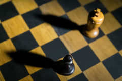 Chess pawn casting a king piece shadow on chessboard concept of strength. And aspirations royalty free stock photo