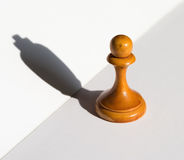 A chess pawn casting a king piece shadow concept of strength aspirations. A chess pawn casting a king piece shadow concept of strength and aspirations stock image