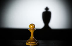 A chess pawn casting a king piece shadow in dark concept of strength plus aspirations Royalty Free Stock Photography