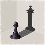 Chess pawn casting a king piece shadow Royalty Free Stock Images
