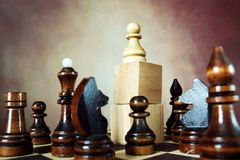 Chess pawn has an supremacy over enemy team because he stands on a high stand. Domination. Concept with chess pieces. Chess pawn has an supremacy over enemy team Royalty Free Stock Image