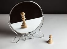 Chess Pawn Looking in the Mirror and Seeing a. Mirror looking king pawn game background copy stock photos
