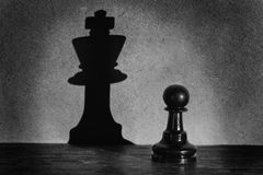 Chess pawn standing in a spotlight that make a shadow  actistic Royalty Free Stock Photos
