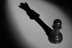 Chess pawn standing in a spotlight that make a shadow of queen a Stock Images