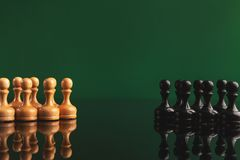 Chess figures on green background with reflection. Chess pawns on green background with reflection. Confrontation of rival pieces for intellectual game, copy Royalty Free Stock Image