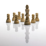 Chess pawns and king/ standing out of the crowd Royalty Free Stock Image