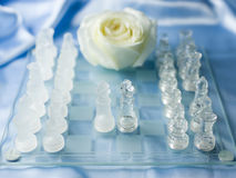 Chess Peace Agreement. Two glass chess figures - kings meeting in the center of a chessboard to conclude a peace agreement, blue satin and white rose in the Stock Photo