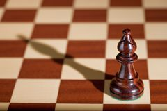 Chess piece - a black bishop on a chessboard. Royalty Free Stock Images