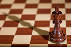 Chess piece - a black king on a chessboard. Royalty Free Stock Images