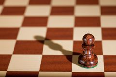 Chess piece - a black pawn on a chessboard. Stock Photos