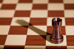 Chess piece - a black rook on a chessboard. Stock Photo