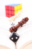 CHESS PIECE WITH DICE ON A BOOK AND RUBIK�S CUBE Royalty Free Stock Photos