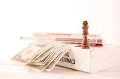 CHESS PIECE, DOLLAR BILLS AND BOOKS Stock Image