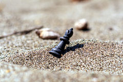 Chess piece Queen in the sand. Chess piece of a Queen lies on the sand on the side Stock Photos