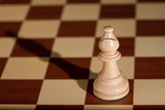Chess piece - a white bishop on a chessboard. Stock Image