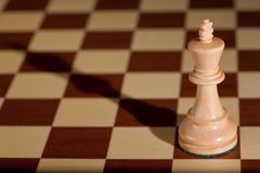 Chess piece - a white king on a chessboard. Royalty Free Stock Photo