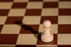 Chess piece - a white pawn on a chessboard. Stock Images