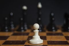 Chess piece white pawn on a chessboard. Chess game. Pawn against all stock images