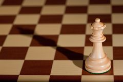 Chess piece - a white queen on a chessboard. Stock Photos