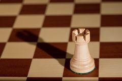 Chess piece - a white rook on a chessboard. Royalty Free Stock Photo