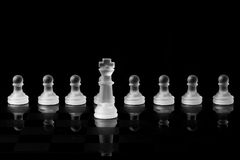 Chess pieces. Frosted glass chess pieces. King in front of pawns Royalty Free Stock Photo