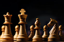 Chess pieces. Image shows chess pieces around the white King, photographed from a low angle and with selective focusing on the king royalty free stock photo