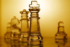 Chess pieces. Transparent chess pieces with yellow light illumination Stock Photography