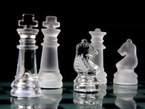 Chess pieces. Made of glass on board over black background royalty free stock photography