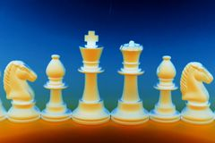 Chess Pieces. Gold Chess Pieces on Blue Background stock images