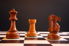 Chess pieces. Queen rook and knight on chessboard Stock Images