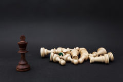 Chess pieces on a black background. The king stands next to the defeated white figures. Stock Photos