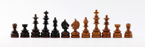 Chess Pieces Black and Brown. Black and brown wood carved chess pieces on white background Royalty Free Stock Photos
